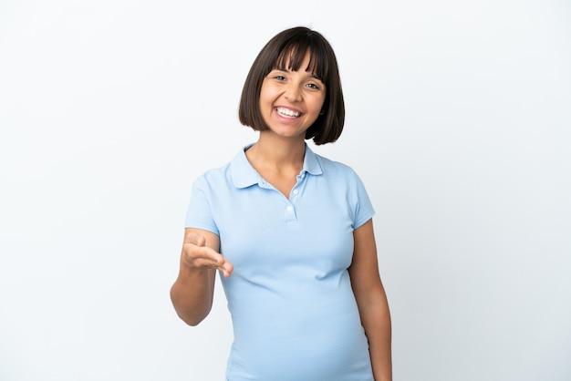 Kobieta w ciąży na białym tle, ściskając ręce, żeby zamknąć dobrą ofertę