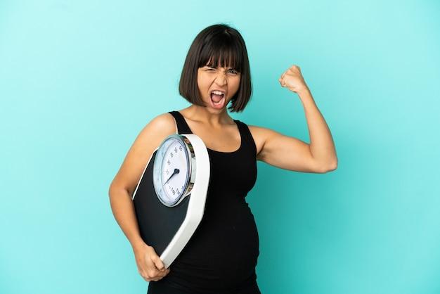 Kobieta w ciąży na białym tle trzymająca wagę i wykonująca silny gest
