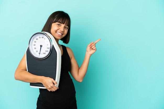 Kobieta w ciąży na białym tle z maszyną do ważenia i wskazującą stronę