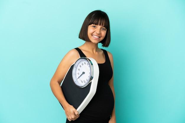 Kobieta w ciąży na białym tle z maszyną do ważenia