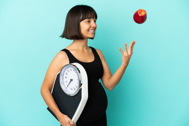 Kobieta w ciąży na białym tle z wagą i jabłkiem