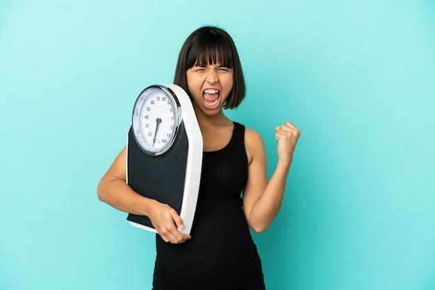 Kobieta w ciąży na białym tle z wagą i wykonującą gest zwycięstwa