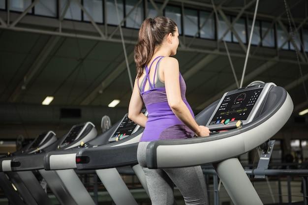 Kobieta w ciąży na bieżni na siłowni