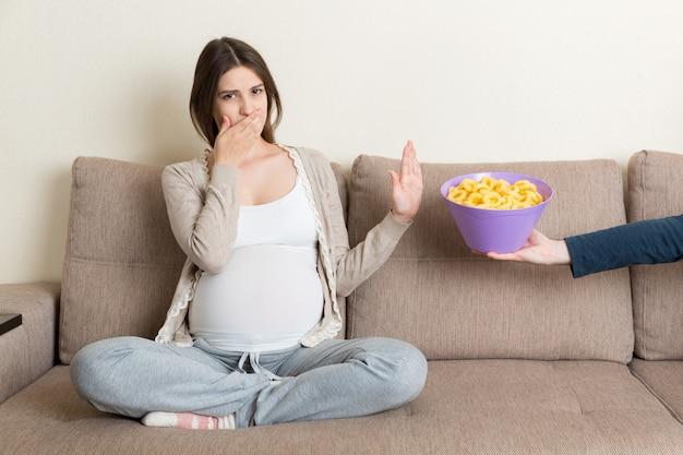 Kobieta w ciąży na sofie odmawia jedzenia niezdrowych przekąsek