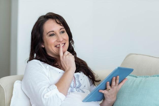 Kobieta w ciąży odpoczywa na leżance używać pastylkę