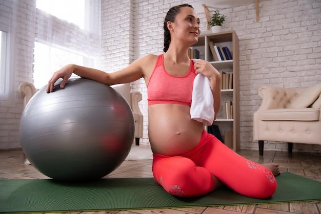 Kobieta w ciąży odpoczywa po treningu w domu