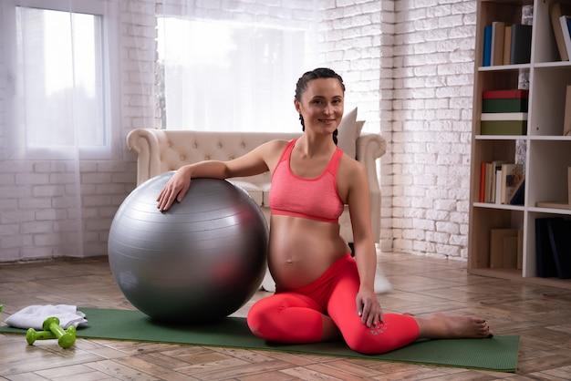 Kobieta w ciąży odpoczywa po treningu.