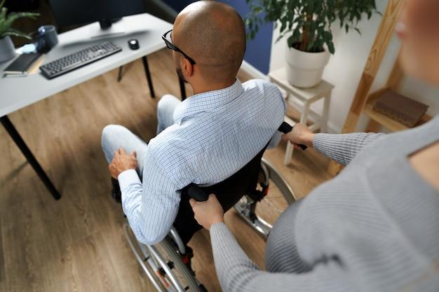 Kobieta w ciąży opiekuje się niepełnosprawnym mężem na wózku inwalidzkim