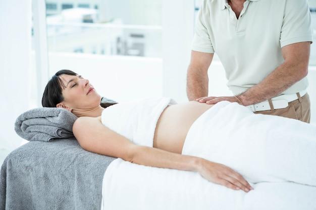 Kobieta w ciąży otrzymująca masaż brzucha od masażysty w spa
