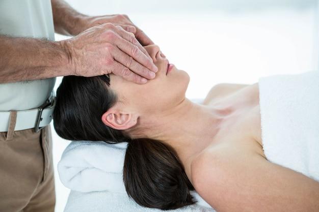 Kobieta w ciąży otrzymująca masaż twarzy od masażysty w spa
