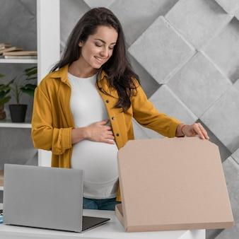 Kobieta w ciąży otwiera pudełko podczas pracy w domu