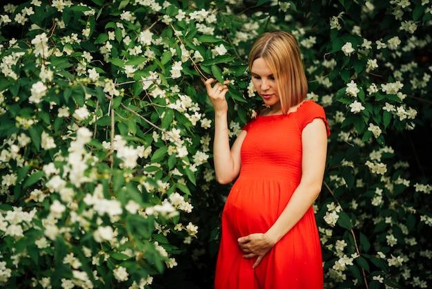 Kobieta w ciąży patrzeje w dół średni strzał