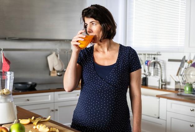 Kobieta w ciąży pije sok pomarańczowego