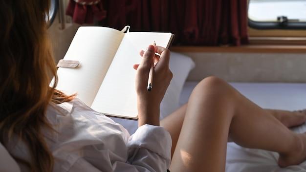Kobieta w ciąży pisania na notebooku w pojeździe rekreacyjnym.