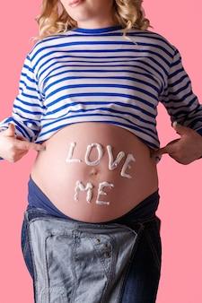 """Kobieta w ciąży pisze na brzuchu słowo """"kochaj mnie""""."""
