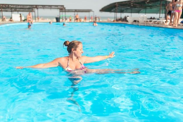 Kobieta w ciąży pływa w basenie na plecach
