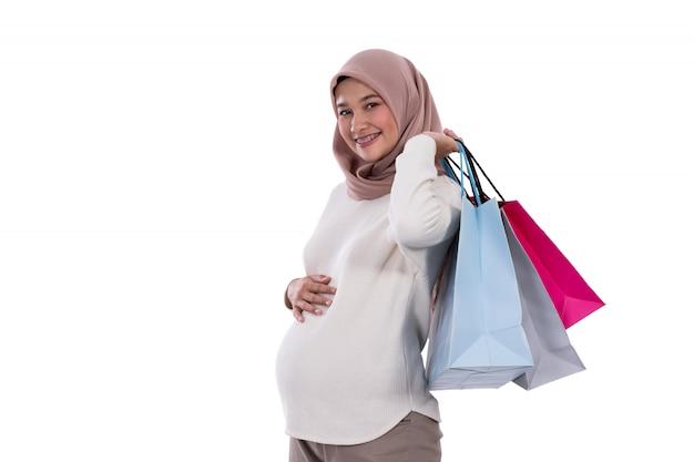 Kobieta w ciąży pokazuje wiele toreb na zakupy