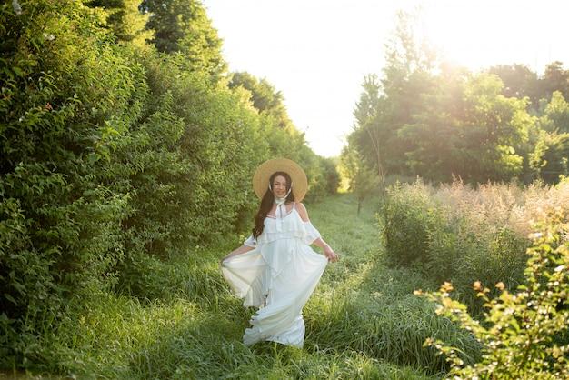 Kobieta w ciąży pozowanie w białej sukni na charakter.