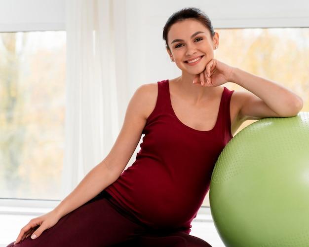 Kobieta w ciąży pozuje obok piłki fitness