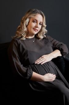 Kobieta w ciąży pozuje w eleganckiej czarnej sukience w pomieszczeniu studio czarnym tle ściany