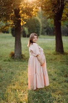 Kobieta w ciąży pozuje w parku