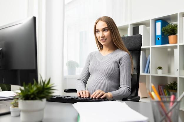 Kobieta w ciąży pracuje przy biurku na komputerze