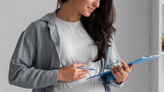 Kobieta w ciąży pracuje w domu ze schowkiem