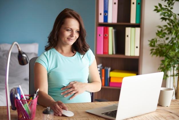 Kobieta w ciąży pracuje w domu