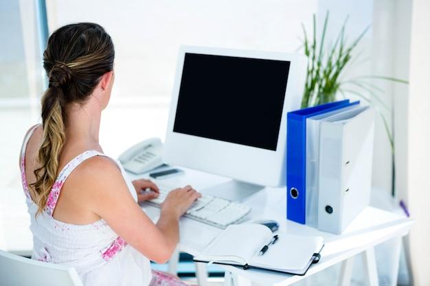 Kobieta w ciąży, przy biurku, na komputerze