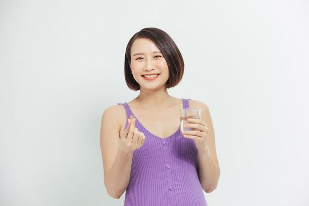 Kobieta w ciąży przyjmuje witaminy. dziewczyna w ciąży ze szklanką wody i garścią leków w dłoni.