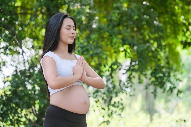 Kobieta w ciąży robi ćwiczenia jogi w przyrodzie