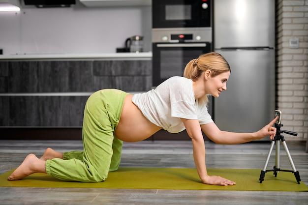 Kobieta w ciąży robi ćwiczenia z kotem w pozycji marjariasany w domu, oglądając lekcję wideo online