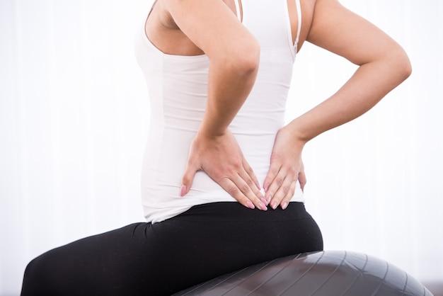 Kobieta w ciąży robi ćwiczenia z powrotem choroby.