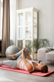 Kobieta w ciąży robi jogę w domu