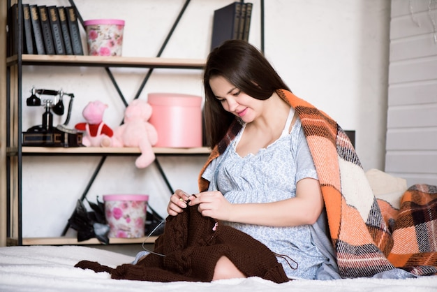 Kobieta w ciąży robi na drutach swoje nienarodzone dziecko na łóżku w domu