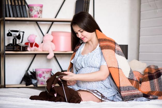 Kobieta w ciąży robi na drutach swoje nienarodzone dziecko na łóżku w domu.