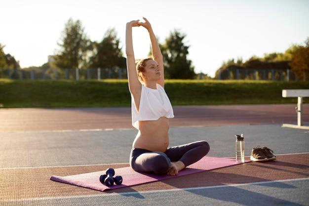 Kobieta w ciąży robi samotnie jogę na świeżym powietrzu