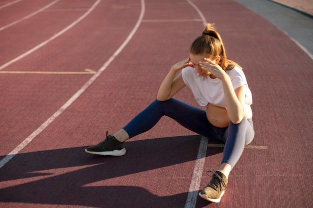 Kobieta w ciąży robi sobie przerwę od ćwiczeń na świeżym powietrzu