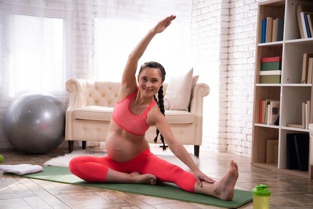 Kobieta w ciąży rozciąga i trenuje brzuch w domu