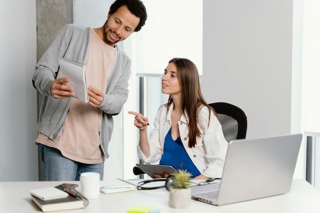 Kobieta w ciąży rozmawia ze swoim współpracownikiem