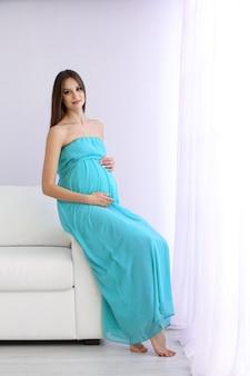 Kobieta w ciąży siedzi na kanapie w pokoju