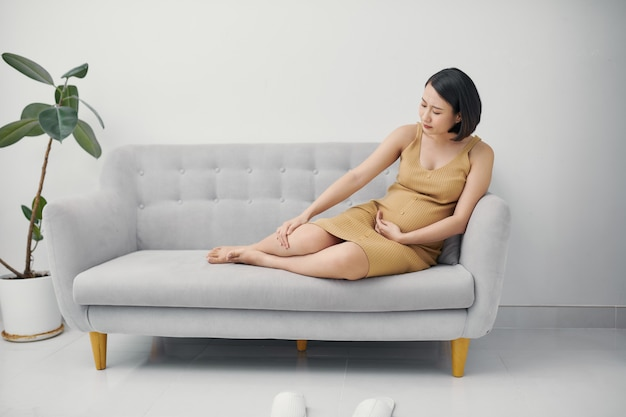 Kobieta w ciąży siedzi na kanapie.