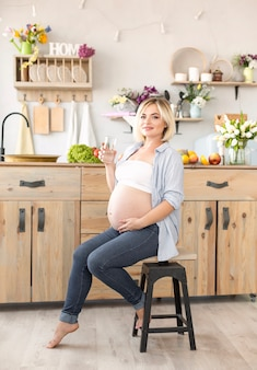 Kobieta w ciąży siedzi na krześle, trzymając szklankę wody