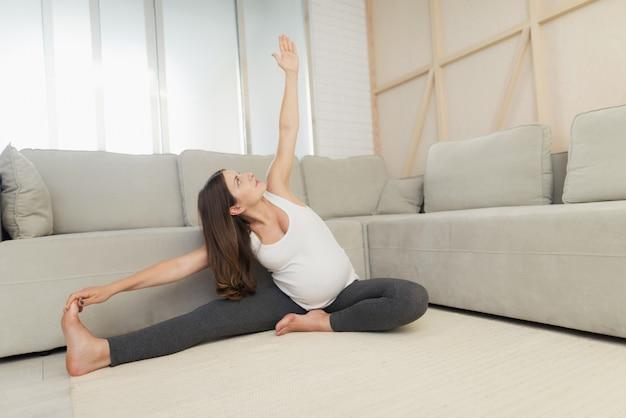 Kobieta w ciąży siedzi na lekkiej podłodze w domu.