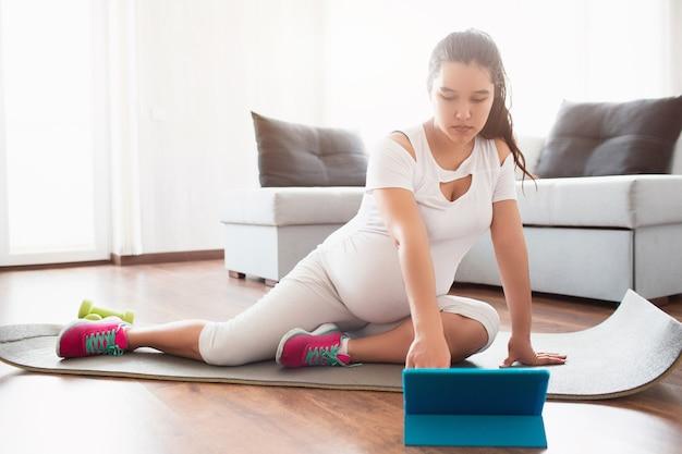 Kobieta w ciąży siedzi na macie do jogi i podczas ciąży korzysta z aplikacji mobilnej na tablecie.
