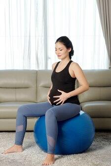 Kobieta w ciąży siedzi na piłce fitness