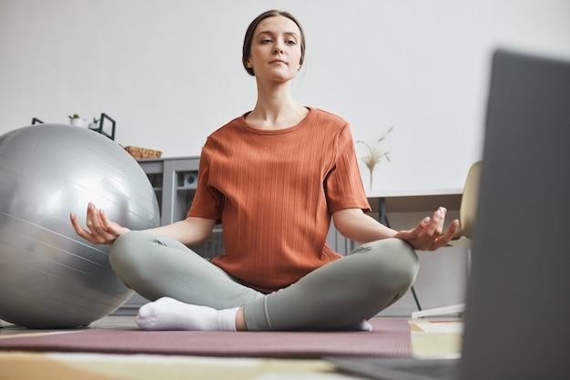 Kobieta w ciąży siedzi na podłodze przed laptopem oglądając lekcję online i medytując w pokoju