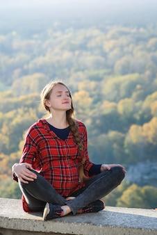 Kobieta w ciąży siedzi na wzgórzu z zamkniętymi oczami