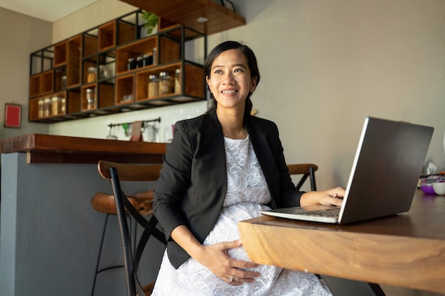Kobieta w ciąży siedzi samotnie podczas korzystania z laptopa