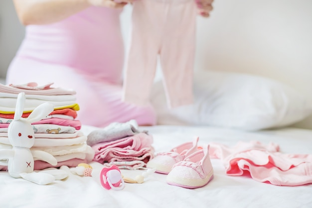 Kobieta w ciąży składa dziecięce rzeczy